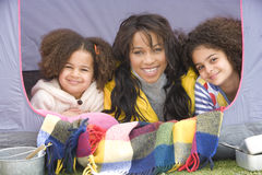 Smiling mother and daughters laying in tent Stock Images