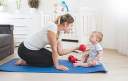 Smiling mother doing physical exercise with her baby on floor at Stock Image