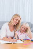 Smiling mother drawing with her daughter Royalty Free Stock Photo