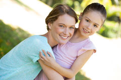 Smiling mother embracing her daughter at park Royalty Free Stock Image