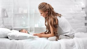 Smiling mother enjoying caress cute baby resting on bed surrounded by white room interior. Full shot. Beautiful European woman having good time with little stock video footage