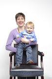 Smiling mother with funny baby. Behind old chair in studio Royalty Free Stock Image