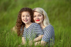 Smiling mother and funny daughter in green grass field. outdoor Royalty Free Stock Photos
