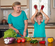 Smiling mother and funny playful daughter cooking together, help children to parents. Stock Photography