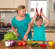 Smiling mother and funny playful daughter cooking together, help children to parents. Royalty Free Stock Photo