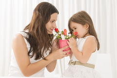 Smiling mother getting flowers from her daughter on mother's Day Royalty Free Stock Images