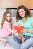Smiling mother getting a heart card from her daughter Stock Image