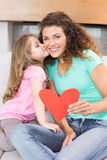 Smiling mother getting a heart card and a kiss from her daughter Stock Photography