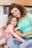 Smiling mother getting little flowers from her cute daughter Stock Photography