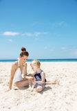 Smiling mother and girl in swimsuits at sandy beach playing Royalty Free Stock Photos