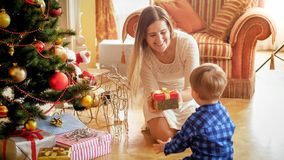 Happy smiling mother giving Christmas gift to her toddler son. Smiling mother giving Christmas gift to her toddler son royalty free stock photo