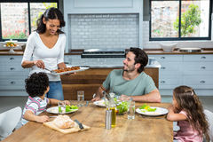Smiling mother giving food to her children and husband Royalty Free Stock Photos