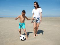 Smiling mother with happy son playing with a ball Royalty Free Stock Photo