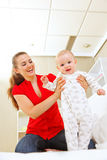 Smiling mother helping baby learn to walk Royalty Free Stock Photography