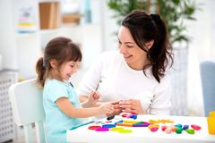 Smiling mother helps a little daughter to sculpt figurines from plasticine. Children`s creativity. Happy family.  stock photography