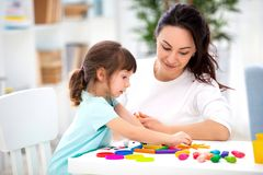 Smiling mother helps a little daughter to sculpt figurines from plasticine. Children`s creativity. Happy family.  royalty free stock photo