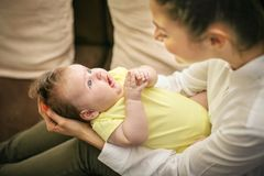 Mother with her baby girl in arms at home. Focus on back royalty free stock images