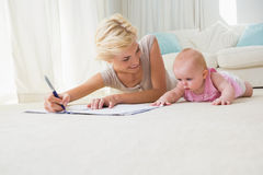 Smiling mother with her baby girl writting on a copybook Stock Photo