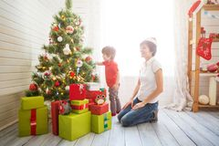 Smiling mother with her beautiful little son decroating Christmas tree with baubles at home stock photos