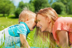 Smiling mother and her child in the green field Royalty Free Stock Image