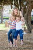 Smiling mother and her children swinging Stock Photos
