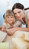 Smiling mother and her daughter decorating a room Royalty Free Stock Photos