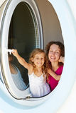 Smiling mother and her daughter look out from window Royalty Free Stock Photo