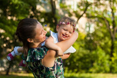 Smiling Mother and her daughter in summer park. Stock Photos