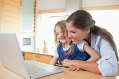 Smiling mother and her daughter using a laptop Stock Photos