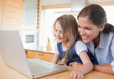 Smiling mother and her daughter using a notebook. In their kitchen Royalty Free Stock Image