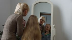 Smiling mother and her girl applying lipsticks stock video