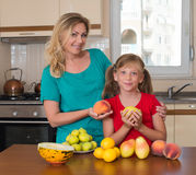 Smiling mother and her keeping sweet pear daughter. Healthy eating - woman and child in the kitchen with different kinds of fruits Stock Photography