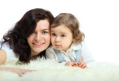 Smiling mother and her little daughter lie Stock Photo