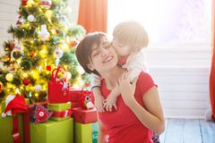 Smiling mother with her little son in living room decorated for Christmas. royalty free stock image