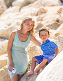 Smiling mother  and her little son. Yellow rocks and stones. Concept of mothers Day. Family outdoors portrait. Stock Photography