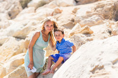Smiling mother  and her little son. Yellow rocks and stones. Concept of mothers Day. Family outdoors portrait. Stock Photo