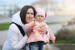 Smiling mother with her serious daughter. Mood difference Royalty Free Stock Photography