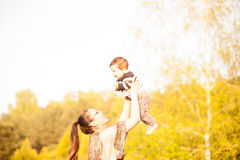 Smiling mother with her son in arms in the park Royalty Free Stock Images