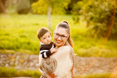 Smiling mother with her son in arms in the park Royalty Free Stock Image