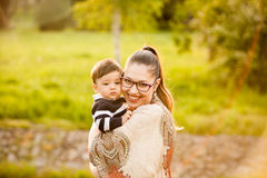 Smiling mother with her son in arms in the park Stock Photos