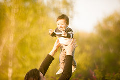 Smiling mother with her son in arms in the park Stock Photo
