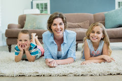 Smiling mother with her son and daughter lying on carpet in living room Royalty Free Stock Photo