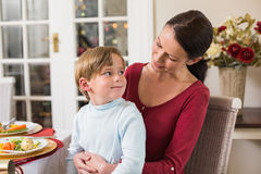 Smiling mother with her son sitting on lap Stock Photo