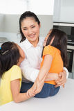 Smiling mother with her young daughters in kitchen Royalty Free Stock Photo
