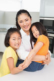 Smiling mother with her young daughters in kitchen Royalty Free Stock Images