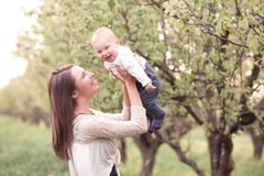 Mother with baby. Smiling mother holding baby boy in park. Childhood. Happiness royalty free stock image