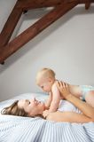Smiling mother holding cute baby in bed royalty free stock photo