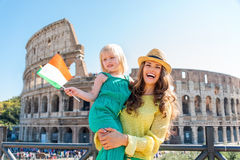 Smiling mother holding daughter with Italian flag and Colosseum. A laughing brunette mother wearing a hat is holding her blonde daughter who is waving an Italian Stock Photos