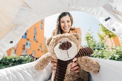 Smiling mother holding teddy bear. In baby stroller royalty free stock photo