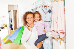 Smiling mother holds shopping bags with daughter Stock Images